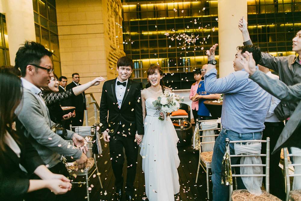 Bride and Groom march in with confetti at Fullerton Bay Hotel